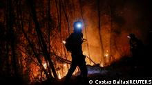 A firefighter is silhouetted as he tries to extinguish a wildfire burning near the village of Ziria, near Patras, Greece, August 1, 2021. REUTERS/Costas Baltas TPX IMAGES OF THE DAY