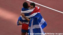 Silver medallist Cuba's Juan Miguel Echevarria (L) and gold medallist Greece's Miltiadis Tentoglou celebrate after the men's long jump final during the Tokyo 2020 Olympic Games at the Olympic Stadium in Tokyo on August 2, 2021. (Photo by Ina FASSBENDER / AFP) (Photo by INA FASSBENDER/AFP via Getty Images)