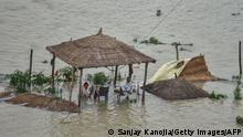 01/08/2021*** TOPSHOT - People sit under a submerged straw hut after the risen water levels in Ganges river flooded the area near the riverbanks, in Allahabad on August 1, 2021. (Photo by SANJAY KANOJIA / AFP) (Photo by SANJAY KANOJIA/AFP via Getty Images)