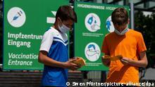 Die Geschwister-Impflinge Hugo (12 Jahre) und Urs (13 Jahre) blättern vor ihrer Impfung am Impfzentrum auf dem Messegelände in ihren Impfbüchern. Bei einer landesweiten Impfaktion für Kinder und Jugendliche wurden rund 27 000 Impfdosen gegen das Coronavirus für den Aktionstag reserviert. +++ dpa-Bildfunk +++