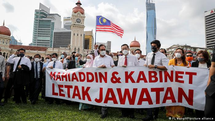 Malaysian opposition members hold a banner reading 'Muhyiddin and Cabinet, resign'