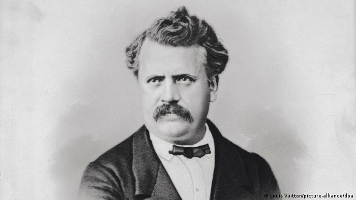 A black and white picture of a man in a suit with a bushy moustache