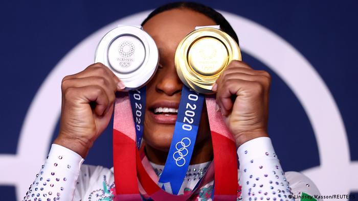 Rebeca segura a medalha de prata em frente a um olho e a de outro em frente a outro.