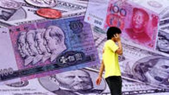 A person speaking on a mobile phone walking past a billboard of Chinese currency