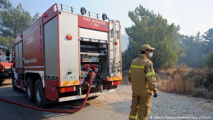 A Greek firefighter battles a forest fire on the island of Rhodes