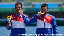 Fernando Dayan Jorge Enriquez, left, and Serguey Torres Madrigal, of Cuba, bite their gold medals after winning the men's canoe double 1000m final at the 2020 Summer Olympics, Tuesday, Aug. 3, 2021, in Tokyo, Japan. (AP Photo/Darron Cummings)