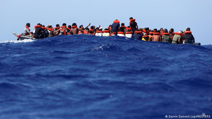 Some 89 migrants on a wooden boat wait to be rescued off the coast of Italy