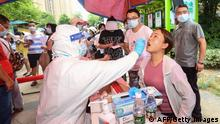 A resident (R) is given a nucleic acid test for the coronavirus in Wuhan in China's central Hubei province on August 3, 2021, as the city tests its entire population for Covid-19. - China OUT (Photo by STR / AFP) / China OUT (Photo by STR/AFP via Getty Images)