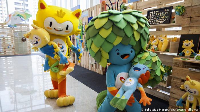 Vinícius e Tom em uma loja. São pessoas com fantasias das mascotes, que carregam pelúcias das mascotes que representam.