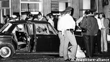 05.08.1971 Das Fluchtauto, das vor der Bank für die Geiselnehmer bereit stand, und in dem einer der Gangster getötet und eine der Geiseln verletzt wurde, nach der Schießerei. Dramatische Stunden und einen großen Polizeieinsatz erlebte München in den Nachmittags- und Abendstunden des 5. August 1971, nachdem zwei schwer bewaffnete, maskierte Männer in einer Filiale der Deutschen Bank in der Prinzregentenstraße Bankangestellte und Kunden als Geiseln festgehalten und zwei Millionen Mark Lösegeld sowie ein Fluchtauto und freies Geleit gefordert hatten. Nach der Übergabe des Geldes verließen die Räuber mit zwei Geiseln die Bank. Dabei kam es zu einer Schießerei, bei der die Geisel Ingrid Reppel, vermutlich durch Schüsse eines der Täter, sowie der 31jährige Geiselnehmer Hans-Georg Rammelmayr tödlich getroffen wurden. Der zweite Geiselnehmer, der 24jährige Dimitri Todorov, wurde verhaftet.