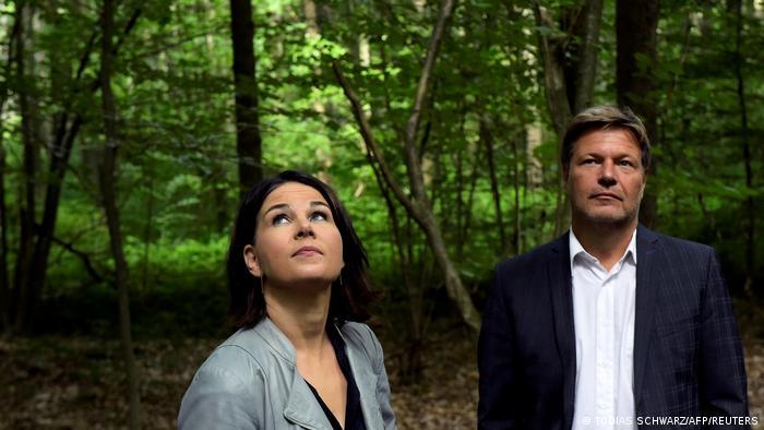 Die Grünen Parteichefs Annalena Baerbock und Robert Habeck stehen in einem Wald und gucken nach oben.