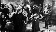 Nazis treiben Juden aus dem Warschauer Getto 1943 zum Abtransport in ein Konzentrationslager zusammen. Hunderttausende von Polen wurden während des Krieges zur Zwangsarbeit nach Deutschland verschleppt. Vor allem die jüdische Bevölkerung Polens, die in Warschau und anderen Städten ein Drittel der Bevölkerung der Einwohner stellte, fiel der deutschen Besatzung zum Opfer. Am 1. September 1939 begann mit dem Überfall auf Polen vor 60 Jahren der Zweite Weltkrieg, dessen Spuren nicht nur in Warschau noch sichtbar sind. dpa (zu dpa-Korr Die Spuren des Krieges sind in Polen noch immer sichtbar vom 24.08.1999) nur s/w +++ dpa-Bildfunk +++