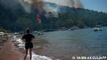 TOPSHOT - A woman watches from a beach the forest burning on August 3, 2021 in Mugla, a Marmaris' district, as Turkey struggles against its deadliest wildfires in decades. - A roaring blaze raced toward a Turkish thermal power plant and farmers herded panicked cattle toward the sea as wildfires that have killed eight people raged on for a seventh day. The nation of 84 million has been transfixed in horror as the most destructive wildfires in generations erase pristine forests and rich farmland across swaths of Turkey's Mediterranean and Aegean coasts. (Photo by Yasin AKGUL / AFP)
