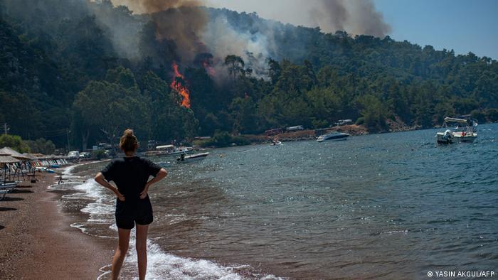 Eine Frau beobachtet die Feuer an der Ägäis