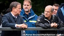 Armin Laschet, Minister President of North Rhine-Westphalia, left, and Olaf Scholz, Federal Minister of Finance, stand on a bridge over the Vichtbach in Stolberg, Germany, Tuesday, Aug.3, 2021. The two candidates for chancellor took a look at the situation and the clean-up work after the floods. (Marius Becker/DPA via AP, Pool)
