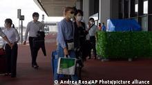 Belarusian Olympic sprinter Krystsina Tsimanouskaya, center left, arrives at Narita International Airport in Narita, east of Tokyo Wednesday, Aug. 4, 2021. (AP Photo/Andrea Rosa)