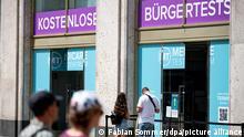 Menschen stehen vor einem Corona-Testzentrum am Alexanderplatz. Hunderte Testzentren waren in den vergangenen Monaten in Berlin entstanden. Mittlerweile ist etwa für den Zugang zu Biergarten oder Freibad kein negatives Ergebnis mehr nötig.