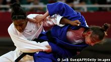 France's Sarah Leonie Cysique (white) and Kosovo's Nora Gjakova compete in the judo women's -57kg final bout during the Tokyo 2020 Olympic Games at the Nippon Budokan in Tokyo on July 26, 2021. (Photo by Jack GUEZ / AFP) (Photo by JACK GUEZ/AFP via Getty Images)
