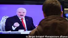 Belarus's President Alexander Lukashenko is seen on TV screens inside a shop, broadcast during a briefing in Minsk, Belarus, Friday, Feb. 3, 2017. In the televised broadcast on Friday, Lukashenko asked the country's interior minister to press charges against Russia's top food safety official, alleging charges of damaging the state because Russia stopped the import of Belarusian products due to quality issues and suspicions that Belarus resells EU-made dairy products that are banned in Russia. The Kremlin responded to the outburst, listing the loans and reduced taxes Russia gave to Belarus. (AP Photo/Sergei Grits)