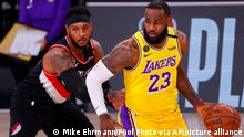 LeBron James, right, of the Los Angeles Lakers drives the ball against Carmelo Anthony, left, of the Portland Trail Blazers during the first half of Game 1 of an NBA basketball first-round playoff series, Tuesday, Aug. 18, 2020, in Lake Buena Vista, Fla. (Mike Ehrmann/Pool Photo via AP)