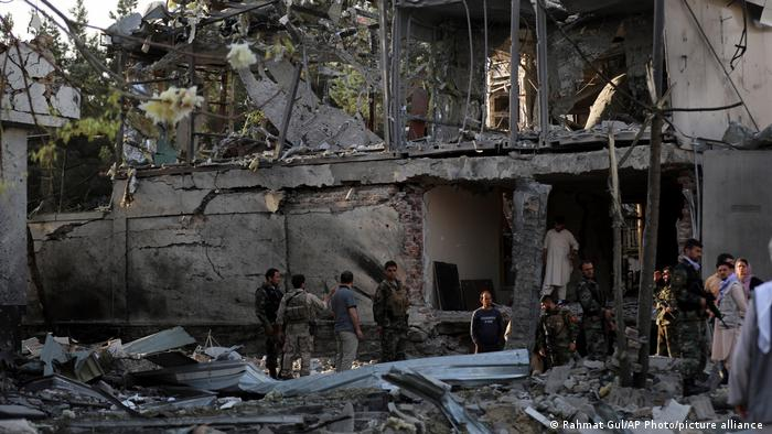 Afghan security personnel inspect the house of acting defense minister following an attack in Kabul