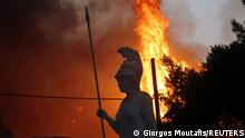 A statue of goddess Athena is seen as wildfire burns at Varympompi suburb north of Athens, Greece, August 3, 2021. REUTERS/Giorgos Moutafis TPX IMAGES OF THE DAY