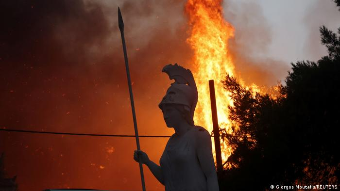 A statue of the goddess Athena is seen against raging flames