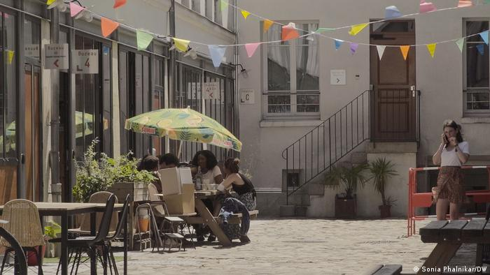 A photo of the Smart Food Paris incubator headquarters courtyard with people sitting under the shade of an umbrella and enjoying their time