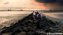 Filmstill SILENCE OF THE TIDES. A film by Pieter-Rim de Kroon.A film that inhales and exhales along with the tides of the Wadden Sea as it explores the fragile relationship between man and nature. 703_Girls on breakwater_ 291_meisjes op strekdam_sott__1.386.1 Synopsis Silence of the Tides is a cinematic tribute to the Wadden Sea, the world's largest, and most varied, uninterrupted intertidal area, extending along the coasts of The Netherlands, Germany and Denmark.