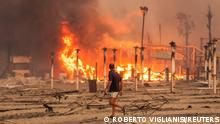 A man walks in front of a fire at Le Capannine beach in Catania, Sicily, Italy, July 30, 2021, in this photo obtained from social media on July 31, 2021. Roberto Viglianisi/via REUTERS THIS IMAGE HAS BEEN SUPPLIED BY A THIRD PARTY. MANDATORY CREDIT. NO RESALES. NO ARCHIVES.