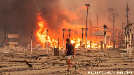 man walks across burnt beach with fire in background