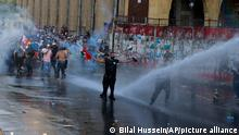 Riot police use tear gas and a water cannon against anti-government protesters during a protest marking the first anniversary of the massive blast at Beirut's port, near Parliament Square, In Beirut, Lebanon, Wednesday, Aug. 4, 2021. United in grief and anger, families of the victims and other Lebanese came out into the streets of Beirut on Wednesday to demand accountability as banks, businesses and government offices shuttered to mark one year since the horrific explosion. (AP Photo/Bilal Hussein)
