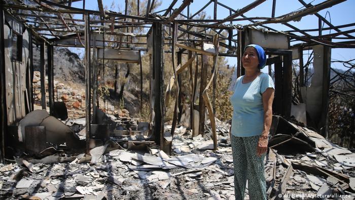 Eine Frau im ausgebrannten Haus