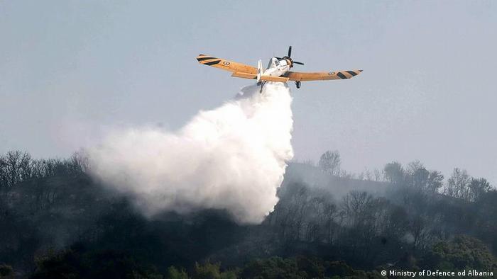 Albanien: Kleines Löschflugzeug lädt Wasser über verbranntem Wald ab