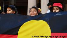 Children hold an Indigenous flag at a rally in Sydney