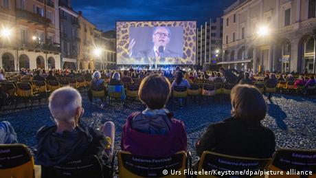 Audience members watch Festival President Luciano Giudici onscreen at the Piazza Grande