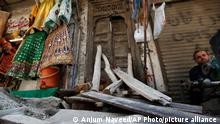 A street vendor waits for customers next to a damaged main door of a Hindu temple, that was vandalized by a group of assailants, in Rawalpindi, Pakistan, Monday, March 29, 2021. Assailants in Pakistan damaged the nearly century-old Hindu temple in the garrison city of Rawalpindi before fleeing the scene. The vandals damaged the door and the stairs of the temple in the attack, which took place on Saturday night, police said. (AP Photo/Anjum Naveed)