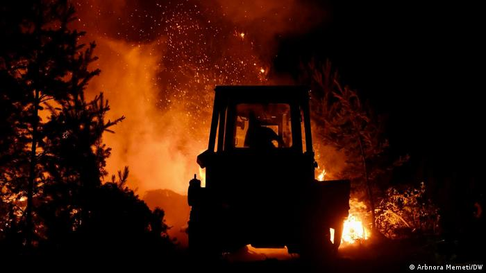A tractor is silhouetted against a raging forest fire in North Macedonia