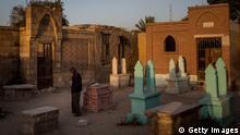 Ein Mann steht vor einem Grabstein in Ägypten