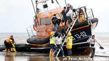 Migrants from nations including Vietnam, Iran and Eritrea disembark a RNLI vessel after being rescued in the English Channel, following their departure from northern France, in Dungeness, Britain, August 4, 2021. REUTERS/Peter Nicholls TPX IMAGES OF THE DAY