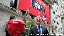 Weber Inc. CEO Chris Scherzinger poses beside a giant grill outside the New York Stock Exchange prior to his company's IPO, Thursday, Aug. 5, 2021. (AP Photo/Richard Drew)