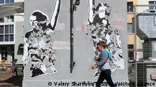 MINSK, BELARUS - SEPTEMBER 15, 2020: A boy walks past a painted over mural depicting DJs Vlad Sokolovsky and Kirill Galanov at Change Square in Chervyakova Street. Sokolovsky and Galanov put on Peremen [Changes], a song by Russian singer Viktor Tsoi, during an event organized by the Belarusian authorities on August 6. The DJs were arrested, spent 10 days in prison and left the country. Utility workers paint over the mural but local residents restore it. Valery Sharifulin/TASS