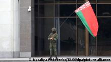 MINSK, BELARUS - SEPTEMBER 6, 2020: A law enforcement officer waves a Belarusian flag outside the Palace of the Republic in Independence Square before the start of the March of Unity held by opposition supporters. Since the announcement of the 2020 Belarusian presidential election results on August 9, mass protests against the election results have been erupting in major cities across Belarus. Natalia Fedosenko/TASS
