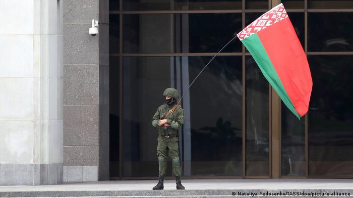 Человек в форме с государственным флагом Беларуси