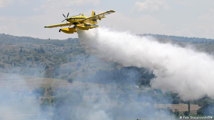 Gelbes Löschflugzeug, das Wasser auf den Wald fallen lässt