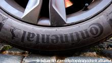 Ein Auto steht mit einem Reifen von Continental auf einer Straße. Continental will noch mehr Standorte schließen als bisher bekannt.