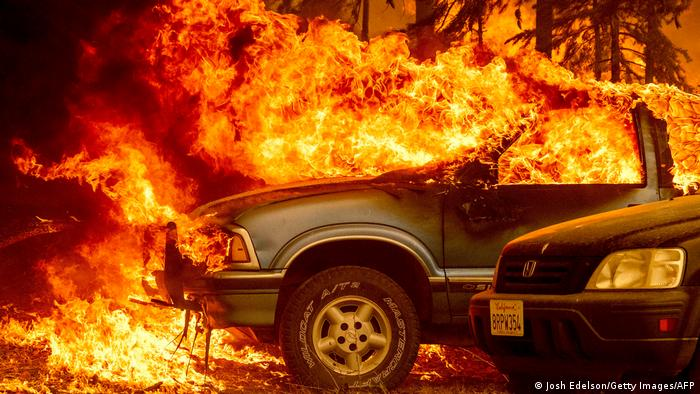 Vehicles and a home are engulfed in flames as the Dixie fire rages on in Greenville, California on August 5, 2021