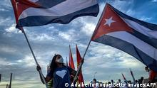 TOPSHOT - A woman holds Cuban flags during a caravan organized by the Union of Young Communists for love, peace and solidarity, along Havana's waterfront on August 5, 2021. (Photo by ADALBERTO ROQUE / AFP) (Photo by ADALBERTO ROQUE/AFP via Getty Images)