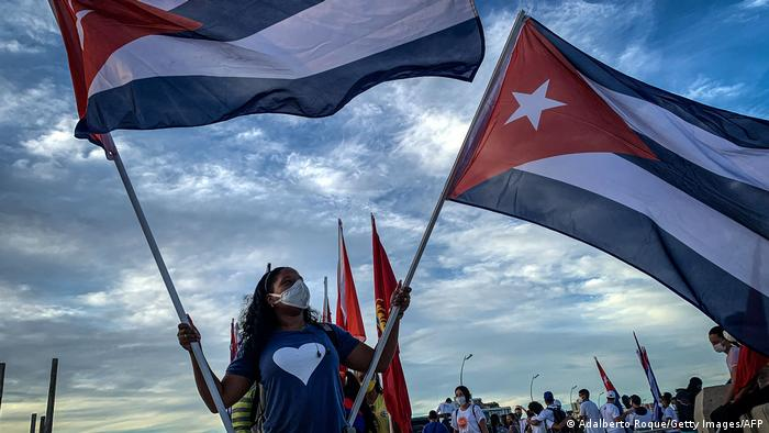 A woman holds Cuban flags during a caravan organized by the Union of Young Communists