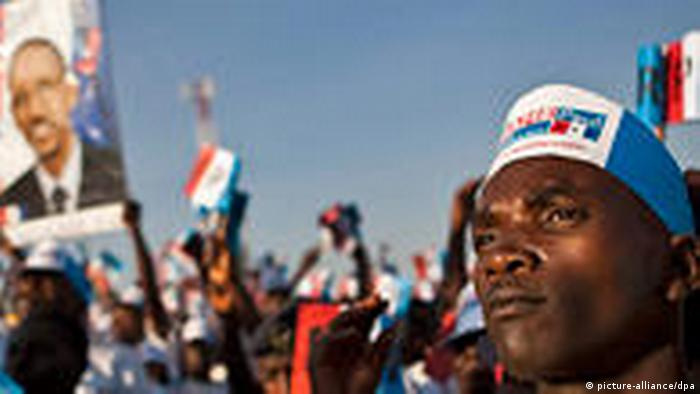 A supporter of Paul Kagame and his party looks on as others cheer at a campaign rally in Kigali